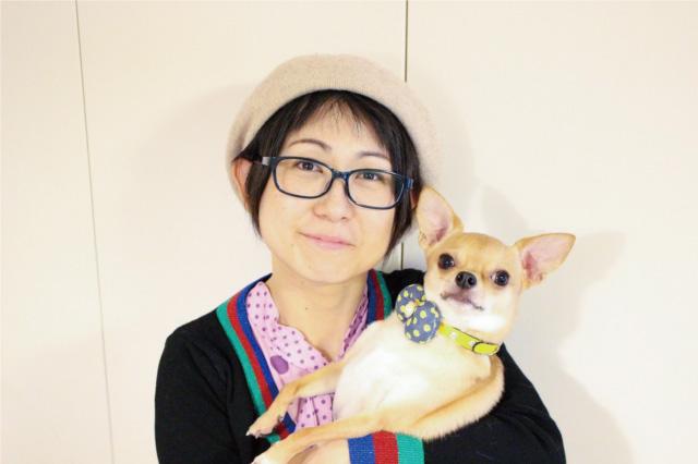 犬を抱いて微笑んでいるトリマー井上恵梨子の写真